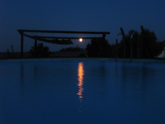La luna piena si riflette sull'acqua della piscina